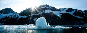 Backlit iceberg floats in a fjord in northern arctic showing a lack of ice floes due to climate crisis